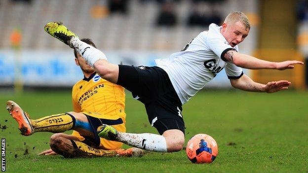 Andrea Orlandi [left] of Brighton & Hove Albion tackles Jack Grimmer of Port Vale