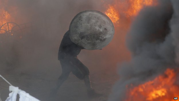 A protester runs amidst fire during a clash with riot police in central Kiev, Ukraine, Saturday 25 January 2014