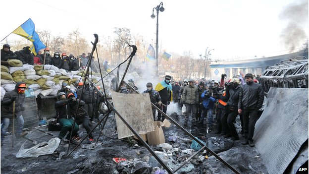 Anti-government protesters use a homemade slingshot to fire a stone during clashes with riot police in central Kiev on 25 January 2014