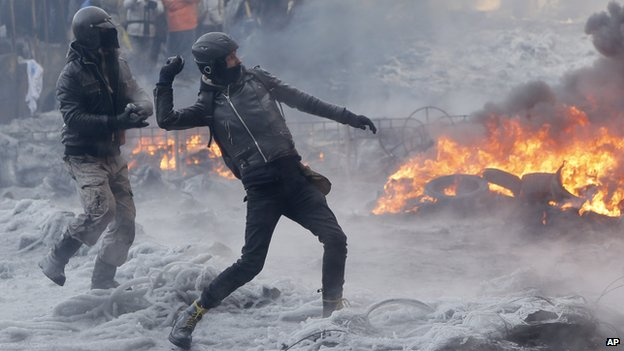 Protesters throw stones towards riot police during a clash in central Kiev, Ukraine, Saturday 25 January 2014