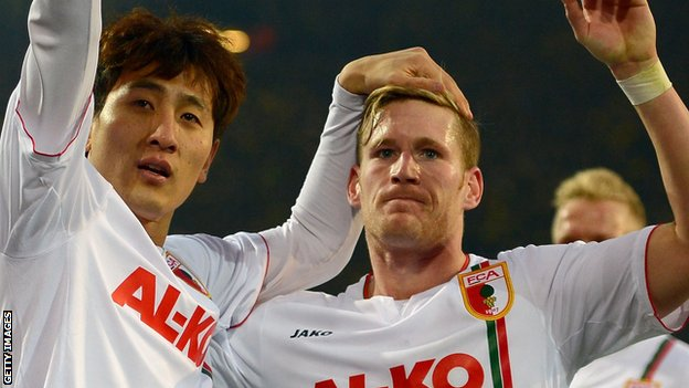 Ji Dong-Won, left, celebrates scoring FC Augsburg's equaliser at Borussia Dortmund.
