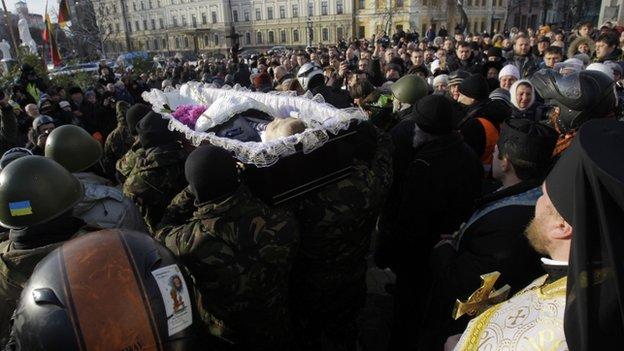 "Crowds chanted ""Hero!"" as the open coffin of Mikhail Zhiznevsky, 25, was carried through the streets of the capital."
