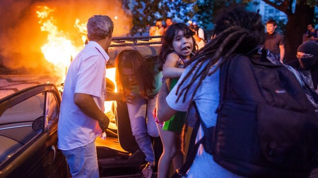 People help a family out of a burning car after it drove over a barricade of fire