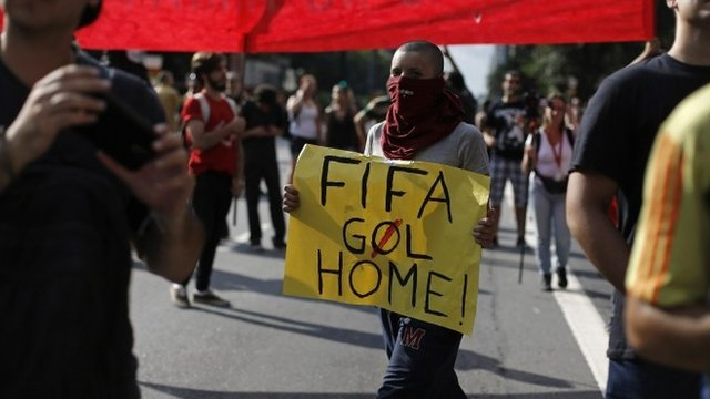 A demonstrator holds a banner that says Fifa 'Goal' Home