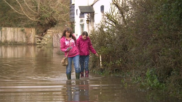 Residents wade through water surrounding a house