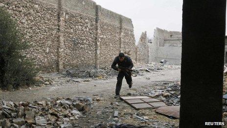 A man carrying a gun runs along a wrecked street