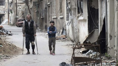 A young boy and a man on crutches stand in a street full of rubble