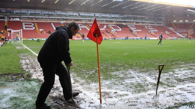 Groundsmen tend to the pitch at Sheffield United's Bramall Lane ground ahead of their FA cup tie with Fulham