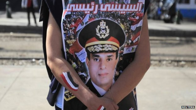 "A woman holding a photo of Gen Sisi with the slogan ""Sisi is my president"""
