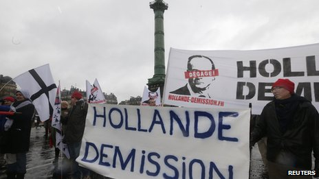 "Demonstrators hold a banner which reads ""Hollande Resign"" as several thousand people attend a Day of Anger march in protest at Mr Hollande's policies"