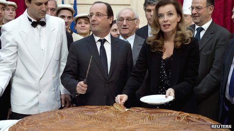 French President Francois Hollande (L) and Valerie Trierweiler (R) cut slices of a giant traditional Epiphany cake during a ceremony at the Elysee Palace in Paris on 7 January 2014