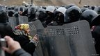 An old lady talks to riot police in Kyiv. Photo: Vincent Mundy
