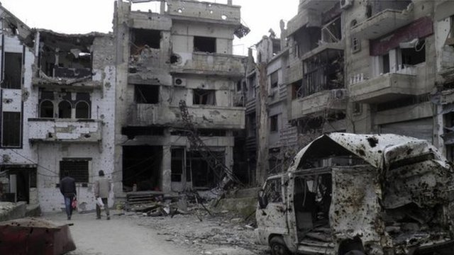 Men walk through damaged buildings in the besieged area of Homs