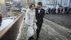 A newlywed couple walks near a barricade built by anti-government protesters in Kiev on Sunday