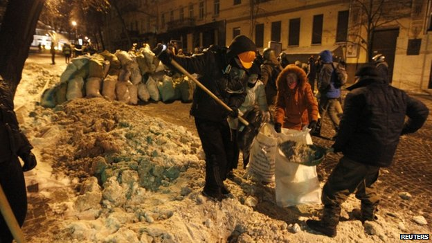 Anti-government protesters fill up sacks with snow to build a barricade along a street at the entrance of the Ministry of Justice in central Kiev 27 January 2014