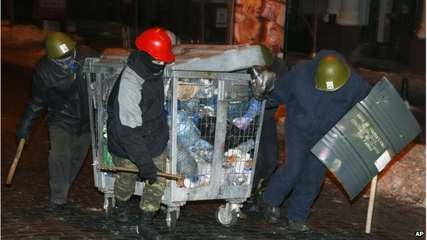 Men pull a cart full of rubbish through Kiev, Ukraine (27 Jan 2014)