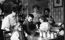 Women and children gathered around a gramophone at home during WW1