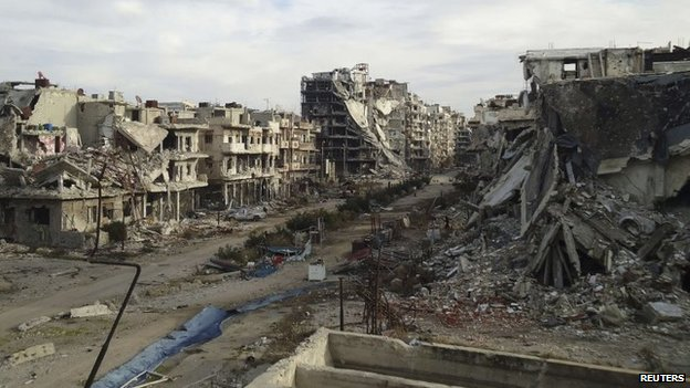 Damaged buildings and debris are pictured in the besieged area of Homs on 24 December 2013