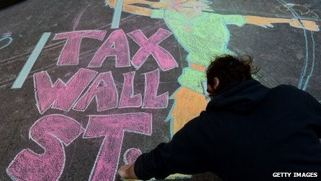 "A protester draws ""tax Wall Street"" on a New York sidewalk using chalk during September 13, 2013, demonstrations"