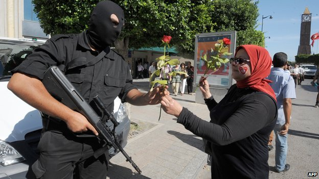 A woman gives a rose to a policeman in  Tunis (23 October 2013)