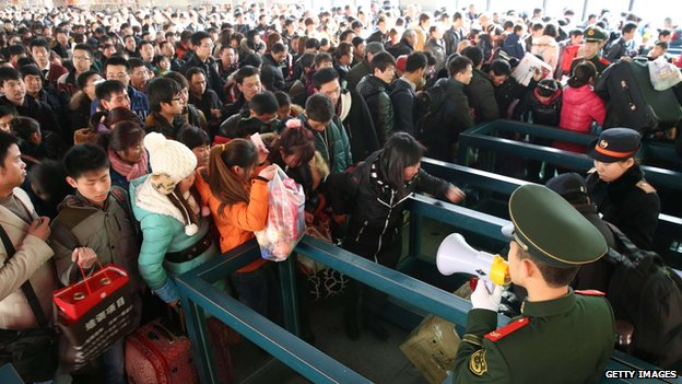 Passengers wait for trains at Beijing West Railway Station on 26 January 2014