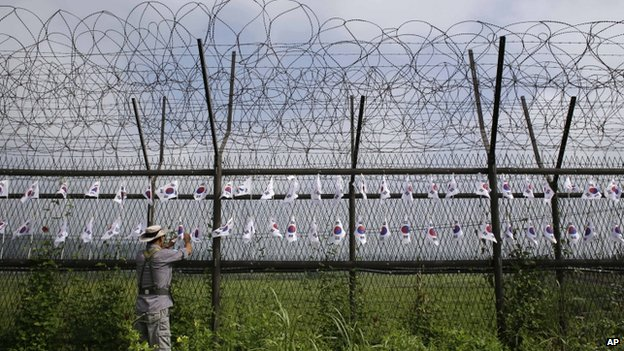A South Korean man adjusts the national flags on the military wire fence at the Imjingak Pavilion near the border village of Panmunjom, which has separated the two Koreas since the Korean War, in Paju, north of Seoul, South Korea, 24 August 2013