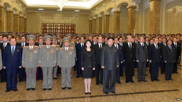 North Korean leader Kim Jong-un, his wife, and high ranking officials stand together in front of statues of the late North Korean leaders, Kim Il-sung and Kim Jong-il in Pyongyang, North Korea, 17 December 2013