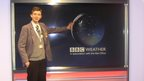 School Reporter Ryan stands in front of the weather forecast screen