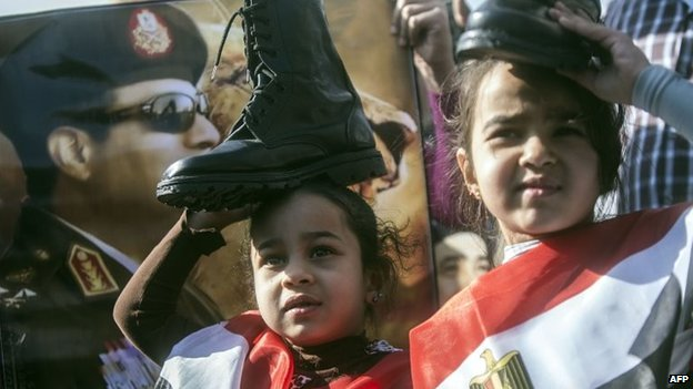 "Supporters of Egypt""s army chief Field Marshal Abdel Fattah al-Sisi (portrait), who is to run for the presidency in the upcoming elections, hold military boots on their heads in a sign of support for military rule"