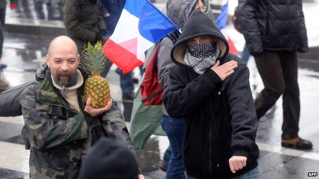 A masked man makes a quenelle gesture in Paris, 26 January