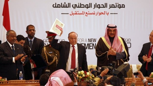 Yemen's President Abdrabbuh Mansour Hadi holds up a copy of the recommendations of the National Dialogue Conference (25 January 2014)