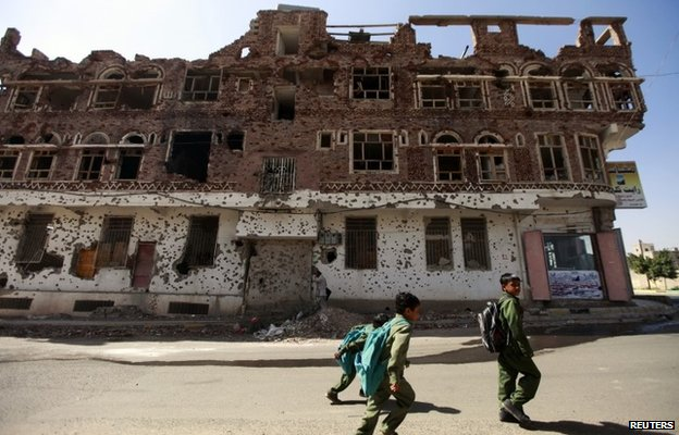 Children walk past a building damaged in the fighting that erupted during the 2011 uprising against former President Ali Abdullah Saleh in Sanaa (17 December 2013)