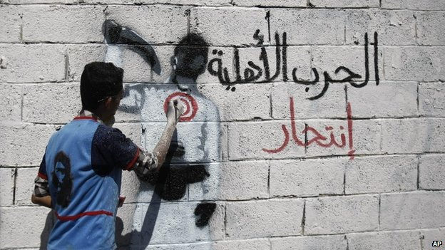 "An activist paints graffiti on a wall in Yemen's capital, Sanaa, that reads: ""Civil war is suicide"""
