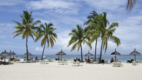 A sunny beach with sun loungers and palm trees