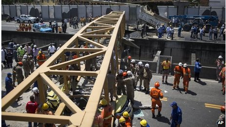Workers attempt to remove a body from under a pedestrian bridge that collapsed after being hit by a truck in Rio de Janeiro, Brazil, on 28 January