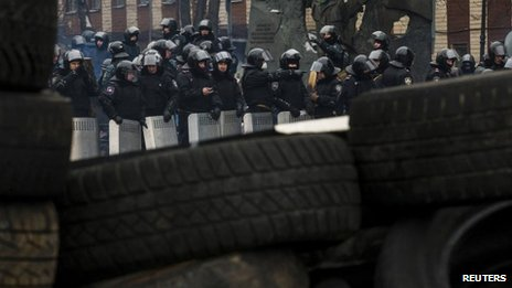 Ukrainian riot police stand in formation facing barricades constructed by anti-government protesters in Kiev, 28 January 2014