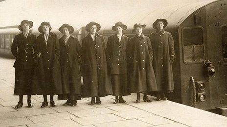 Female underground workers stand beside a train