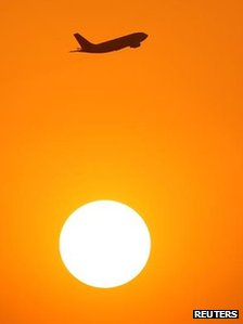 A plane in flight, with the sun below it in the shot