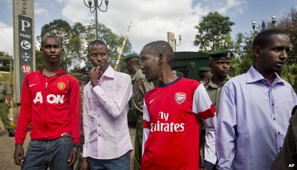 Four ethnic Somalis accused of aiding the Westgate gunmen are escorted by police around the mall (21 January 2014)