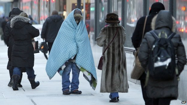 A homeless man bundled up in blankets in Chicago, Illinois, on 28 January 2014