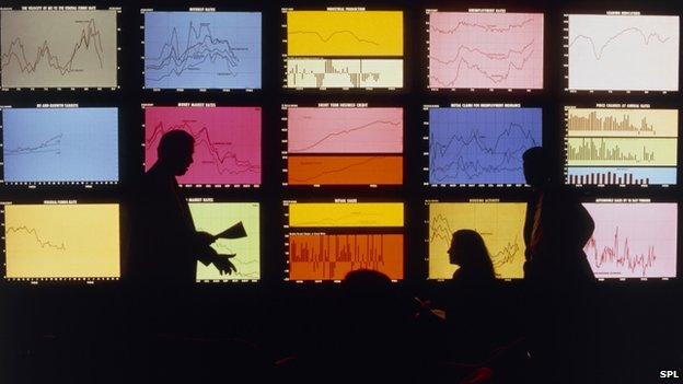 Economists look at a bank of screens