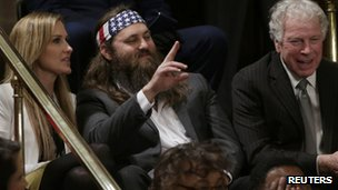 Duck Dynasty television show star Willie Robertson waves as he sits with his wife Korie (L) in the visitor's gallery of the U.S. House of Representatives before the start of U.S. President Barack Obama's State of the Union speech on Capitol Hill in Washington 28 January 2014