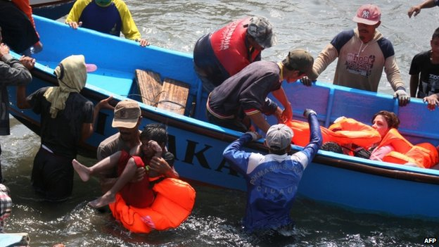 Rescuers assist survivors arriving on fishing boat at the wharf of Cidaun, West Java on 24 July 2013
