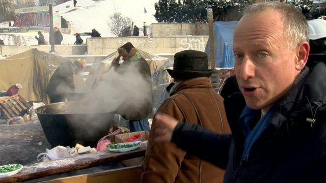 Steve Rosenberg pointing at food stall in Kiev