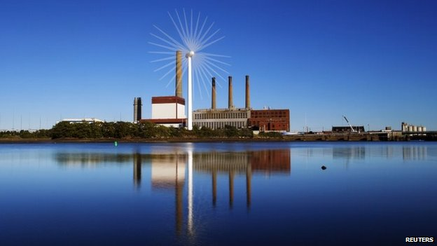 A Massachusetts Water Resources Authority wind turbine turns in front of a 1951 megawatt fossil fuel power plant in Charlestown, Massachusetts