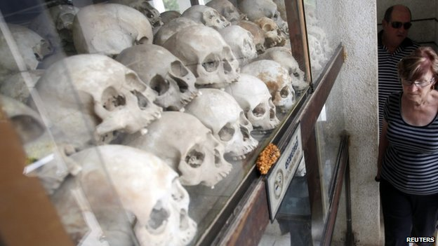 "Tourists visit at a memorial stupa with bones of more than 8,000 victims of the Khmer Rouge regime at Choeung Ek, a ""Killing Fields"" site located on the outskirts of Phnom Penh, 16 October 2013"