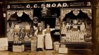 A black and white photograph of a greengrocer and his shop.
