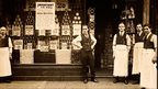 An early 20th century grocer stands proudly outside his shop.