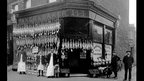 A 1910 poultry shop with rows of different types of birds hanging from the shop front.