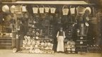 An ironmonger stands in front of his shop.